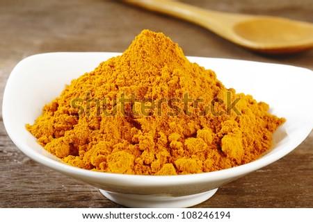 turmeric powder in white dish - stock photo