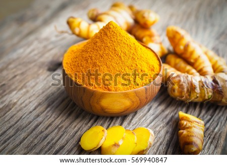 Turmeric powder in wood bowls on wooden table. herbal