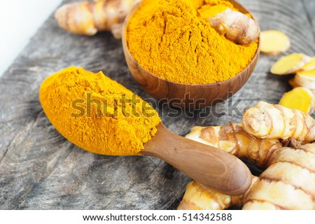 Turmeric powder in wooden spoon on wooden table. herbal