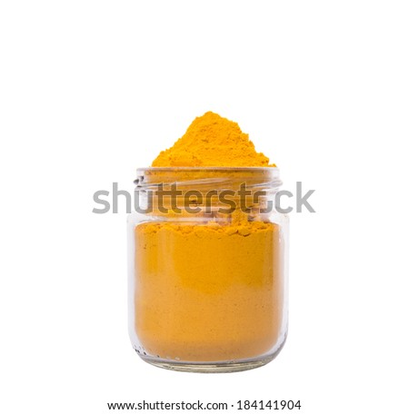 Turmeric powder spice in glass container over white background - stock photo