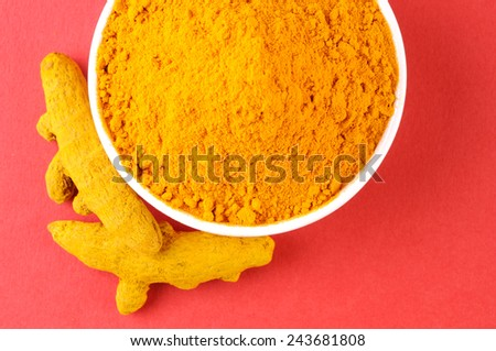 turmeric powder with turmeric on red background - stock photo
