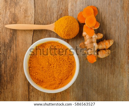 Turmeric roots with turmeric powder on wooden background,top view