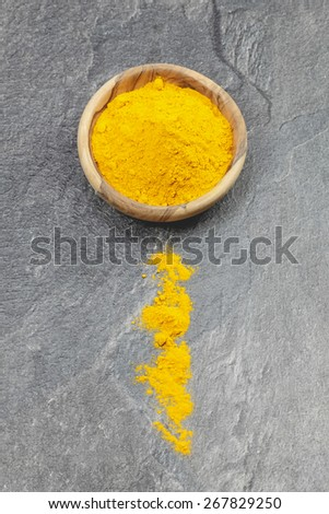 Turmeric. Top angle view of turmeric powder  in olive wood bow. Macro, selective focus  - stock photo