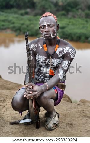 TURMI, ETHIOPIA - 12 AUGUST: unidentified man from Karo tribe in his village near Omo River, Ethiopia, on august 12, 2014. Karo tribes are famous for their body painting - stock photo