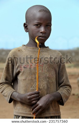 TURMI, ETHIOPIA - NOVEMBER 22, 2011: Portrait of the african boy with the burning candle in hands. November 22, 2011 in Turmi, Ethiopia. - stock photo