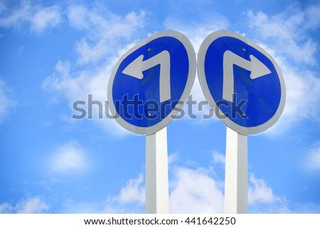 Turn left and turn right arrow sign on blue sky with cloud background for giving directions - stock photo