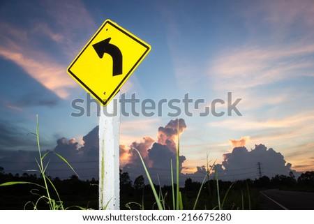 turn left on background of sunset sky - stock photo