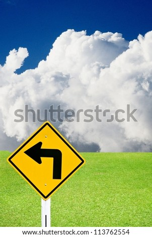 Turn left sign with nice green meadow and cloudy sky