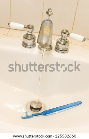 Turn off the tap !  Water conservation awareness depicted by a toothbrush at the bottom of a bathroom sink with the water turned on. Can also be used for dental, tooth hygiene concept. - stock photo