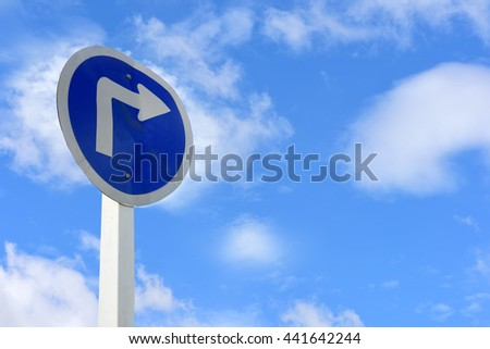 Turn right arrow sign on blue sky with cloud background for giving directions - stock photo
