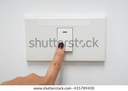 Turn the light switch off to save energy - stock photo