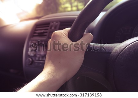 Turn the steering wheel while driving with warm light vintage. Car interior detail. - stock photo