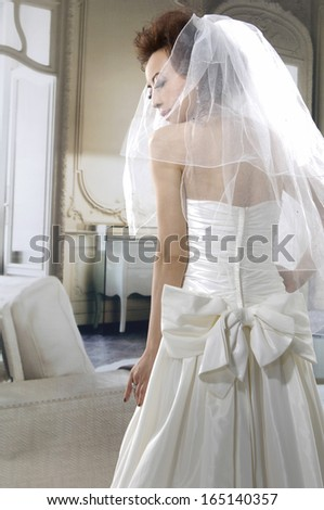 turned of portrait of beautiful young bride in white wedding dress