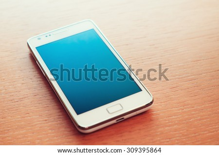 Turned off smartphone on wooden background - stock photo