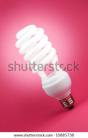 Turned on fluorescent light spiral bulb on pink background - stock photo