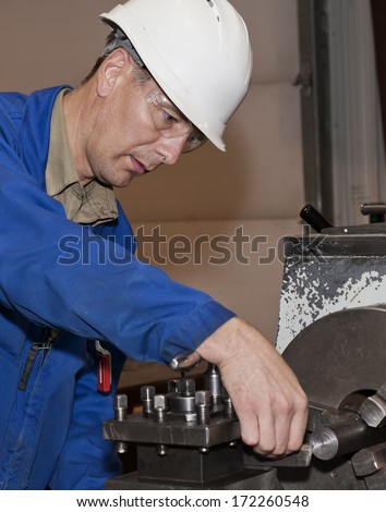 Turner is working on the machine. Metal processing.worker works on a lathe.  - stock photo