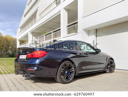 TURNHOUT-APRIL 22, 2017. BMW M4 in front of apartment building. The BMW M4 is a high-performance version of the BMW 4 Series. The renumbering splits 3 Series coupe and convertibles into the 4 Series.
