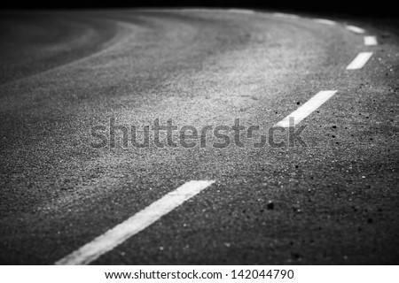 Turning asphalt road with marking lines and tire tracks. Close up photo with selective focus - stock photo