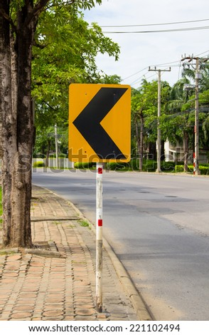 Turning left road sign on roadside and empty road - stock photo