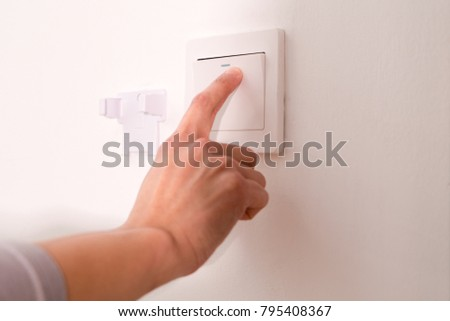 turning off/on the wall-mounted electric light switch.