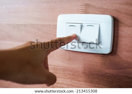 Turning off  on wooden wall-mounted light switch - energy saving concept - stock photo