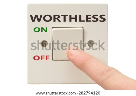 Turning off Worthless with finger on electrical switch - stock photo