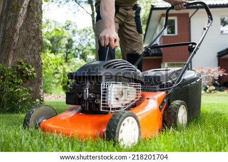 Turning on the lawn mower by gardener - stock photo