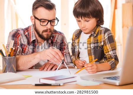 Turning their dreams to reality. Concentrated young man using compass for drawing while sitting at his workplace with his son - stock photo