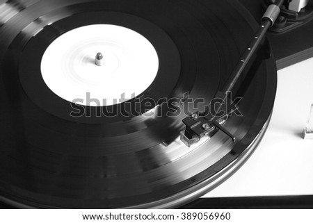 Turntable in silver case playing a vinyl record with white label. Horizontal photo top view closeup - stock photo