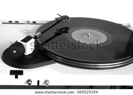Turntable in silver case with rotation vinyl record with red label isolated on white background. Horizontal black and white photo rear view closeup