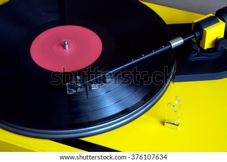 Turntable in yellow case playing a vinyl record with red label. Horizontal photo closeup - stock photo