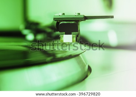 Turntable player with musical vinyl record. Useful for DJ, nightclub and retro theme. Bright green color filter - stock photo