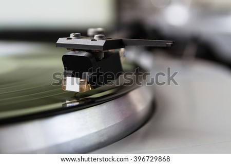 Turntable player with musical vinyl record. Useful for DJ, nightclub and retro theme. Focus on the needle - stock photo
