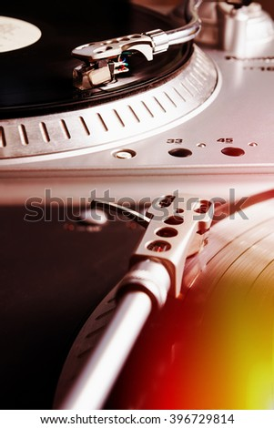 Turntable player with musical vinyl record. Useful for DJ, nightclub and retro theme. Light leak effect - stock photo