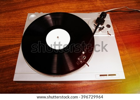 Turntable player with musical vinyl record. Useful for DJ, nightclub and retro theme. Light leak film hipster filter effect - stock photo