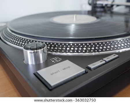 Turntable playing vinyl close up - stock photo