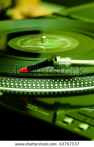 Turntable playing vinyl record with music. Audio equipment for professional DJ, party, concert. Analog sound technology for music lovers or professional musicians.Turntables needle in focus