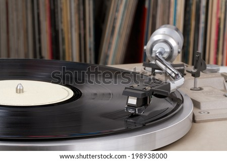 Turntable with vinyl records in the back - stock photo