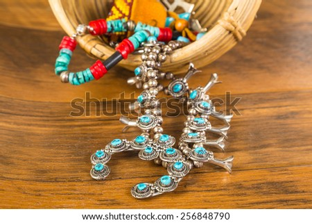 Turquoise and coral and silver Native American jewelry spilling from vintage wicker basket onto old wooden board floor. - stock photo