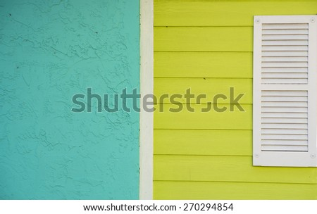 Turquoise and Yellow Exterior Wall of a House with White Window Shutter - stock photo