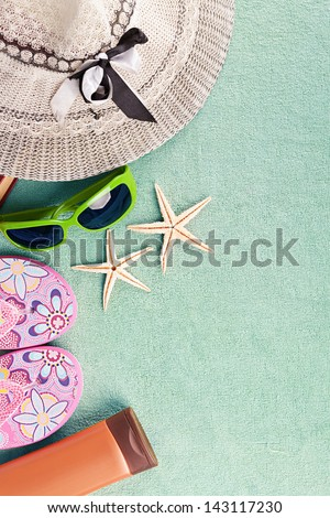 turquoise beach towel with several summer stuff - stock photo