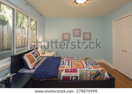 Turquoise Blue Children bedroom / kids room with sports blanket, carpet and view window. - stock photo
