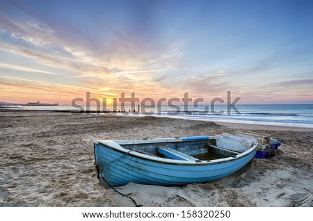 Turquoise blue fishing boat at sunrise on Bournemouth beach with pier in far distance - stock photo