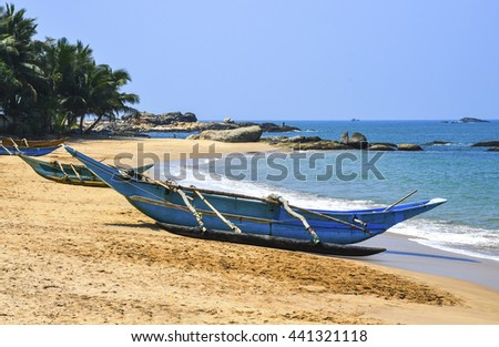 Turquoise blue fishing boat at sunrise on the beach in Sril Lanka, India - stock photo