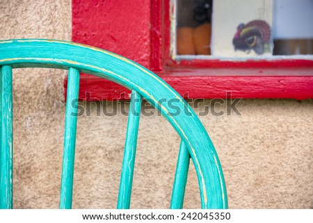 Turquoise colored antique chair sitting in front of a red window frame on Canyon Road in Santa Fe, NM - stock photo