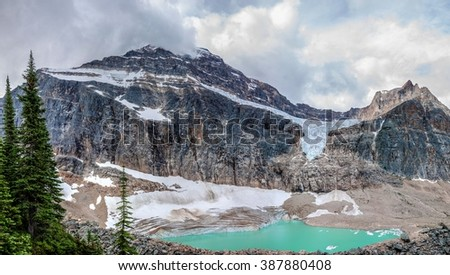 Turquoise lake and snow capped mountain. Mount Edith Cavell and  Edith Cavell meadows,  Jasper National park, Alberta, Canada. - stock photo
