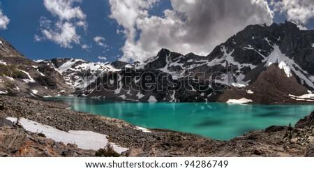 Turquoise mountain lake with cloud shadows panorama - stock photo