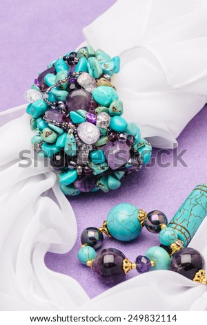 Turquoise necklace and bracelet lying purple background with white scarf - stock photo