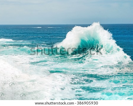 Turquoise ocean wave breaking the sea water on rough sea, with water foam and blue water  Porto Moniz Madeira. - stock photo
