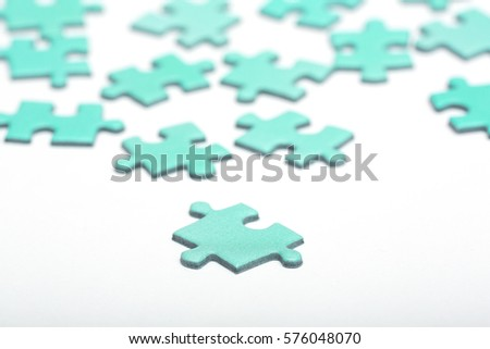 Turquoise puzzle pieces on a white surface. Focus point on the piece in front.